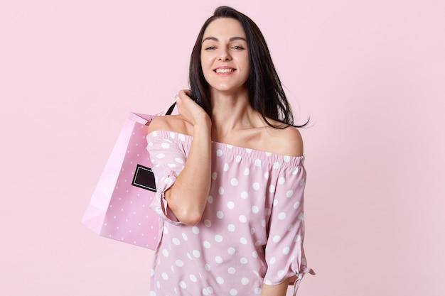 Binnen schot van glimlachende vrouw met lang haar, draagt boodschappentas, verheugt zich het kopen van nieuwe outfit, gekleed in roze polka dot jurk, modellen over licht roze studio muur. vrouwen, aan- en verkoop