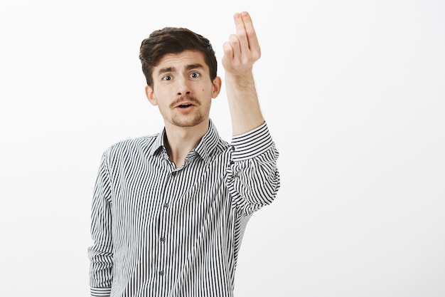 Binnen schot van grappige gewone europese man met snor en baard, hartstochtelijk praten terwijl het verhogen van de hand met italiaans gebaar