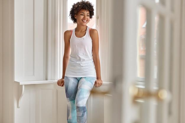 Binnen schot van het positieve mooie vrouw poseren in haar huis