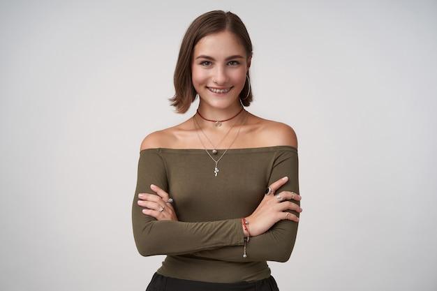Binnen schot van jonge aantrekkelijke bruinharige vrouw die haar handen gekruist houdt terwijl ze poseren over een witte muur, positief naar de voorkant kijkend met een charmante glimlach
