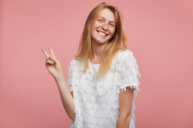 Binnen schot van jonge aantrekkelijke roodharige dame gekleed in elegante kleding terwijl poseren op roze achtergrond, hand opsteken met overwinning gebaar en gelukkig glimlachen naar de camera