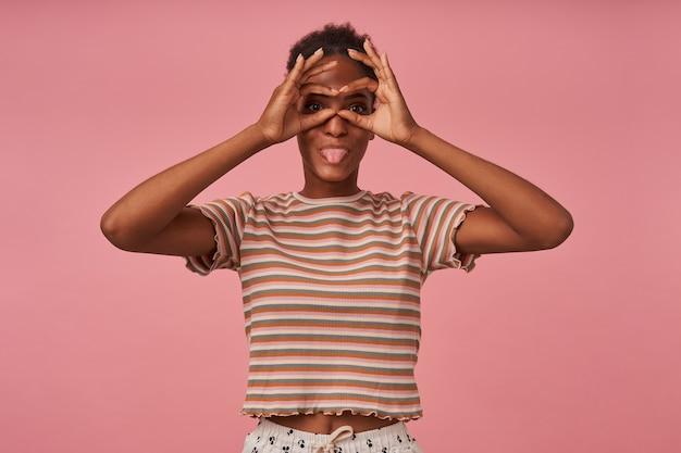 Binnen schot van jonge brunettened vrouw die een bril vormt met haar handen en vreugdevol tong toont terwijl ze over de roze muur in een gestreept t-shirt staat
