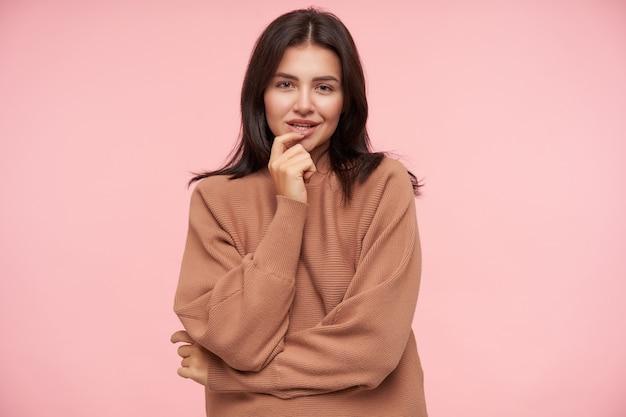 Binnen schot van jonge flirterige mooie brunette vrouw die wijsvinger op haar onderlip houdt en positief naar voren kijkt met een lichte glimlach, staande over de roze muur
