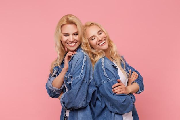 Binnen schot van jonge mooie blonde dames met golvend kapsel rug aan rug leunend terwijl poseren op roze achtergrond in vrijetijdskleding en vrolijk lachen