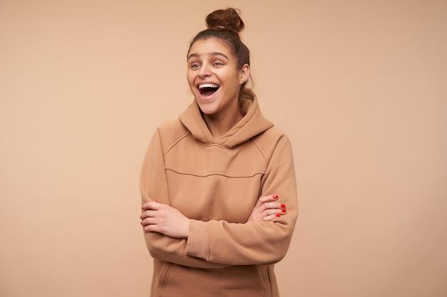 Binnen schot van jonge mooie bruinharige dame met rode manicure die in hoge geest is en gelukkig lacht terwijl ze over beige muur met gekruiste armen staat