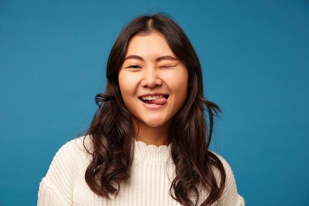 Binnen schot van jonge mooie donkerharige aziatische dame die haar oog gesloten houdt