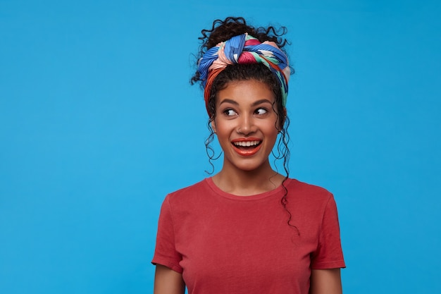 Binnen schot van jonge mooie donkerharige gekrulde vrouw met neuspiercing opgewonden opzij kijken met een brede glimlach, staande over blauwe muur met handen naar beneden