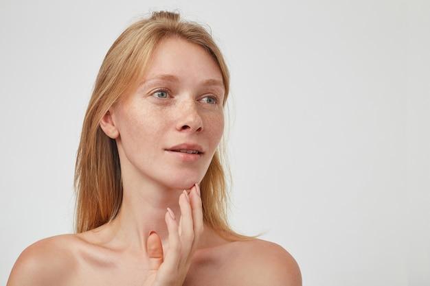 Binnen schot van jonge mooie roodharige vrouw met casual kapsel positief opzij kijken en zachtjes haar gezicht met vingers aanraken, geïsoleerd over witte muur