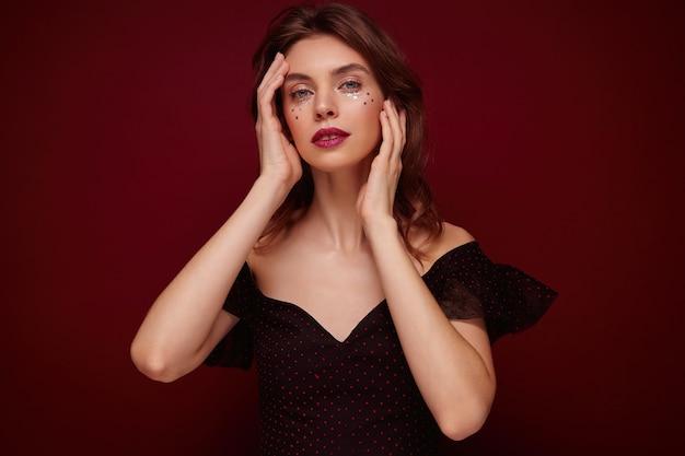 Binnen schot van jonge mooie vrouw met bruin golvend haar zachtjes haar gezicht aanraken en rustig kijken, elegante zwarte top met rode stippen dragen