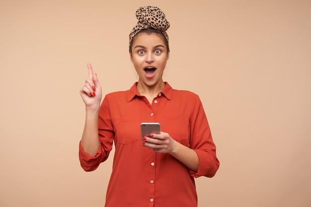 Binnen schot van jonge opgewonden donkerbruine dame gekleed in rood overhemd die hand met ideeteken opheft en emotioneel naar voorzijde kijkt, geïsoleerd over beige muur