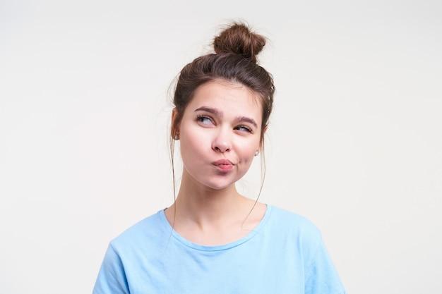 Binnen schot van jonge peinzende bruinharige dame met natuurlijke make-up die haar mond verdraait terwijl zij bedachtzaam opzij kijkt, geïsoleerd over witte muur