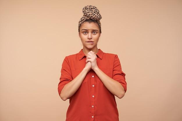 Binnen schot van jonge verbijsterde bruinharige vrouw met hoofdband die opgeheven handen vouwt terwijl ze zorgelijk naar voren kijkt, staande over beige muur