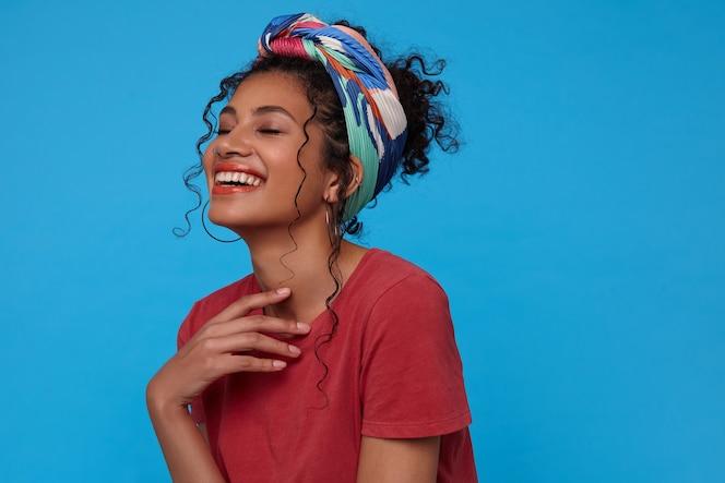 Binnen schot van jonge vrolijke donkerharige vrouw die opgeheven hand op haar borst houdt en gelukkig met gesloten ogen lacht, geïsoleerd over blauwe muur