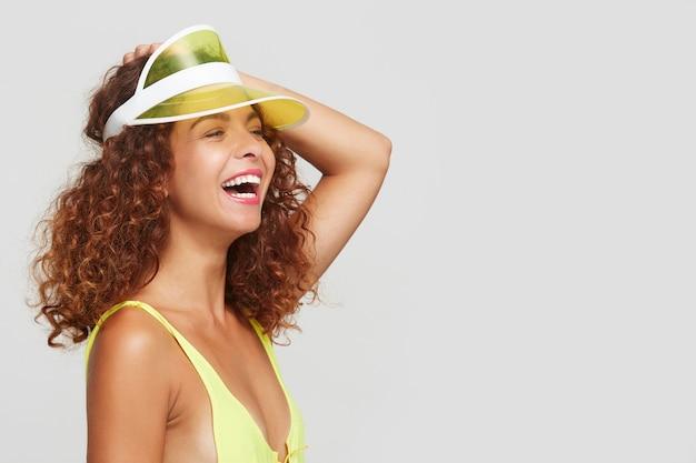Binnen schot van jonge vrolijke roodharige krullende dame met casual kapsel die haar hand op het hoofd houdt terwijl ze gelukkig lacht, geïsoleerd op witte achtergrond