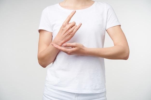 Binnen schot van jonge vrouw die opgeheven handen voor zichzelf houdt terwijl ze werkkind toont dat gebarentaal gebruikt voor doven, staande op witte achtergrond
