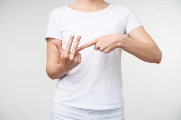 Binnen schot van jonge vrouw gekleed in vrijetijdskleding handen opsteken tijdens het praten over gebarentaal, woord tellen tonen terwijl poseren op witte achtergrond