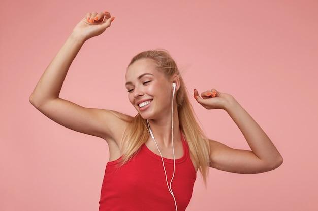 Binnen schot van jouful jonge vrouw in rood shirt met oortelefoons, genieten van muziek en dansen brandgevaarlijk, staande