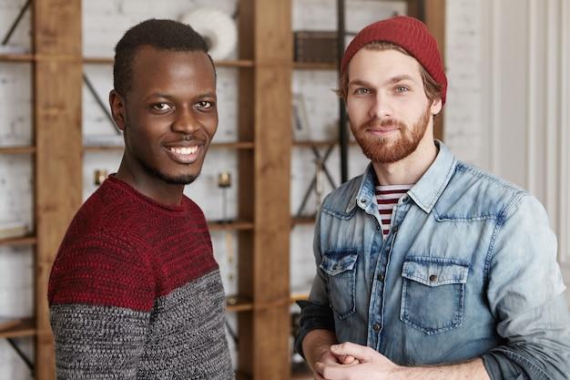Binnen schot van knappe afrikaanse man in gezellige trui staande naast zijn bebaarde hipster vriend