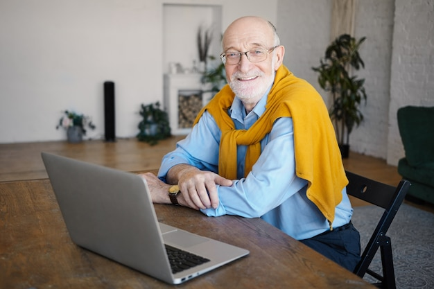 Binnen schot van knappe positieve ongeschoren zestigjarige man schrijver draagt een bril en stijlvolle kleding die in de verte zit aan bureau voor open laptopcomputer, breed glimlachend