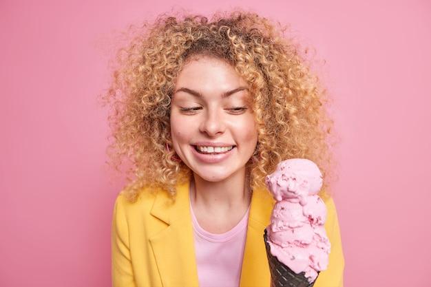 Binnen schot van knappe vrolijke europese vrouw glimlacht gelukkig kijkt naar smakelijk roze ijs in zwarte wafel draagt gele jas heeft natuurlijk krullend haar geïsoleerd over roze muur
