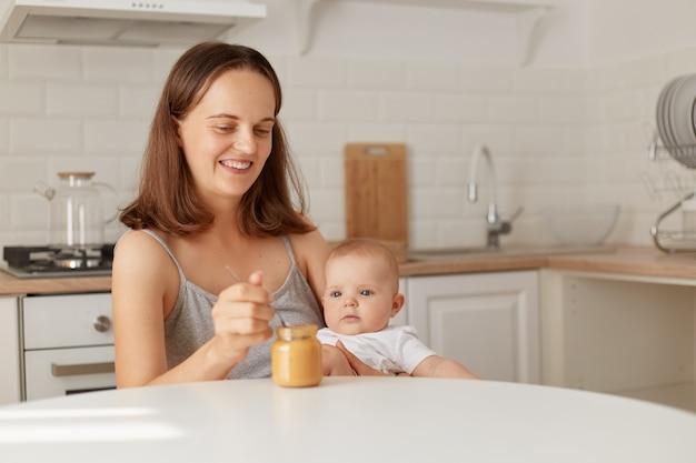 Binnen schot van lachende vrouw zittend aan tafel in de keuken met babymeisje in handen en dochter voeden met fruit of groentepuree, aanvullende voeding van een kind.
