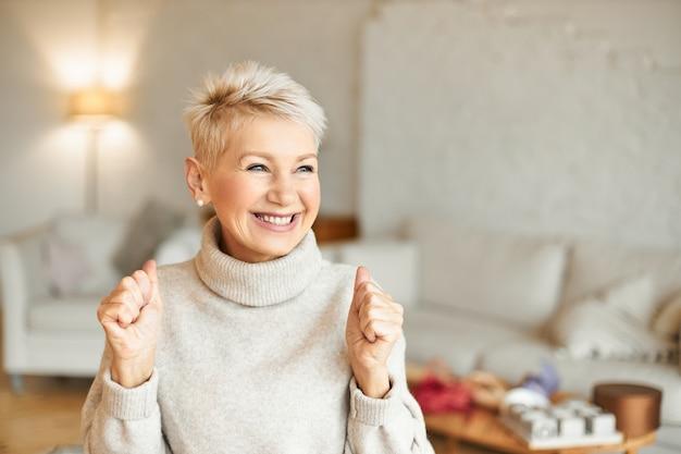 Binnen schot van modieus dolblij volwassen vrouwtje in coltrui genieten van positief nieuws, met extatische gelaatsuitdrukking, lachen en gebalde vuisten. succes en prestaties concept