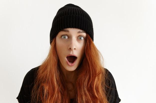 Binnen schot van modieuze verbaasde tiener met losse gemberhaar die zwarte hoed draagt