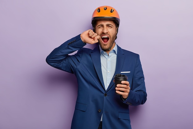 Binnen schot van moe overwerkte zakenman poseren in stijlvol pak en rode helm op kantoor