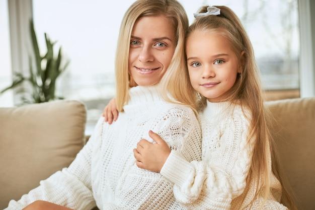 Binnen schot van mooi meisje omarmen haar aantrekkelijke jonge vrouw handen houden om haar middel, beide gekleed in gezellige warme truien, met vrolijke, gelukkige glimlach, plezier maken
