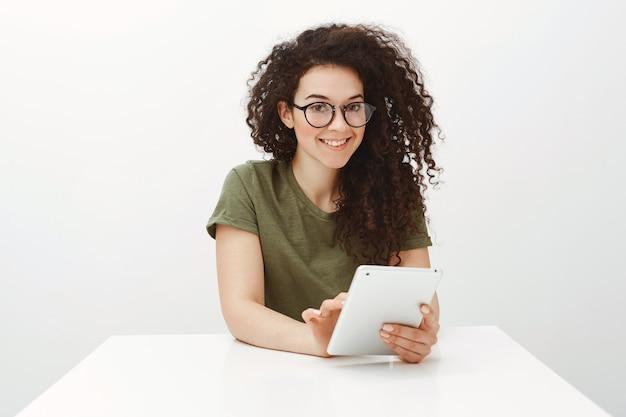 Binnen schot van mooie brunette in zwarte bril, zittend aan witte tafel en browsen in netwerk via digitale tablet
