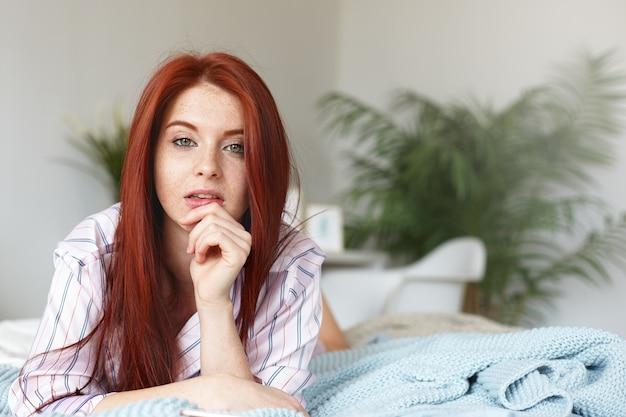 Binnen schot van mooie jonge gember europese vrouw gekleed terloops poseren op bed in gezellige slaapkamer interieur, liggend op de buik en haar kin bedachtzaam aanraken, met dromerige gezichtsuitdrukking
