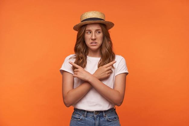 Binnen schot van mooie jonge roodharige krullende vrouw in boot hoed staande met gekruiste armen op haar kuis, wijzend met wijsvingers in verschillende richtingen