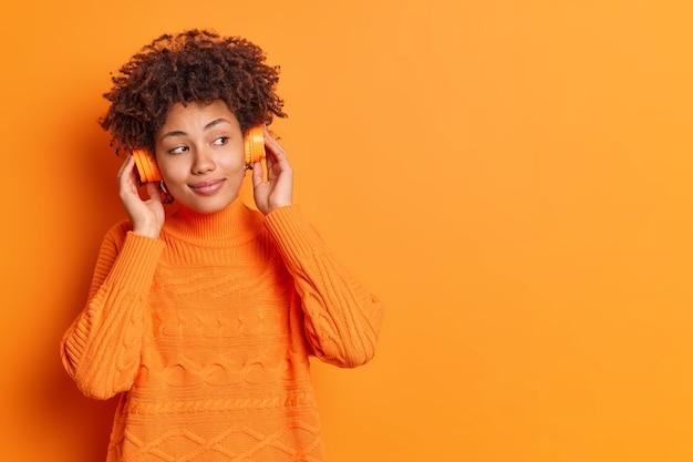 Binnen schot van mooie tevreden vrouw houdt handen op stereo koptelefoon luistert audiotrack heeft kalme uitdrukking gekleed in casual trui geïsoleerd over oranje muur