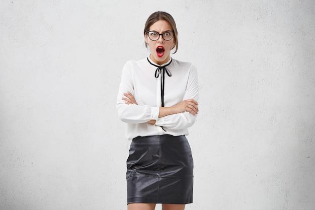Binnen schot van onderwijzeres kijkt met afgeluisterde ogen en geopende mond