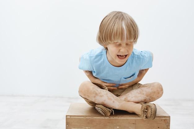 Binnen schot van ongelukkig europees kind met blond haar en vitiligo zittend met gekruiste voeten, schreeuwen en schudden met gesloten ogen
