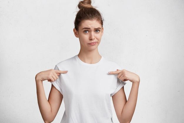 Binnen schot van ongelukkige jonge schattige vrouw met blauwe ogen, haarknoop, gekleed in een casual wit t-shirt, geeft op lege kopie ruimte van t-shirt aan, adverteert kleding, geïsoleerd op studio achtergrond.