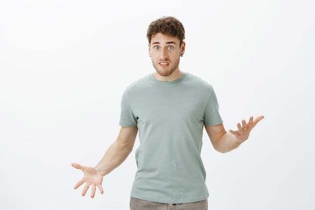 Binnen schot van ontevreden boos aantrekkelijke man in casual t-shirt, gebaren met gespreide handpalmen en staren