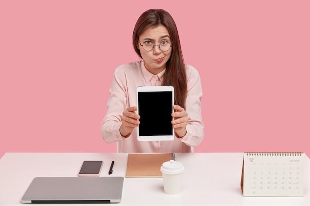 Binnen schot van ontevreden europese vrouw portemonnees lippen, houdt moderne tablet met mock-up scherm voor uw advertentie