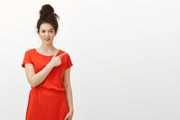 Binnen schot van ontevreden niet onder de indruk aantrekkelijke vrouw in schattige jurk, wijzend naar de rechterbovenhoek met een dubbel teleurgestelde uitdrukking