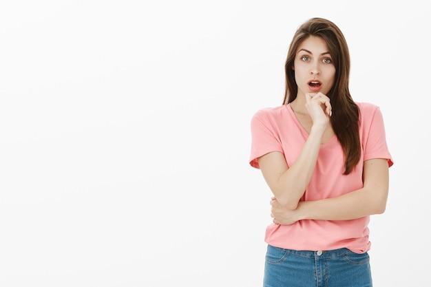 Binnen schot van onverschillige brunette vrouw poseren in de studio