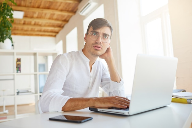 Binnen schot van peinzende geconcentreerde jonge zakenman draagt een wit overhemd op kantoor