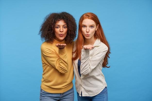 Binnen schot van positieve charmante jonge mooie vrouwen die hun handpalmen opheffen en lippen vouwen terwijl ze een luchtkus blazen, staande tegen een blauwe muur