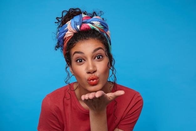 Binnen schot van positieve jonge bruinogige brunette gekrulde vrouw die de handpalm omhoog houdt terwijl ze luchtkus blaast aan de voorkant, staande over de blauwe muur in gekleurde kleding
