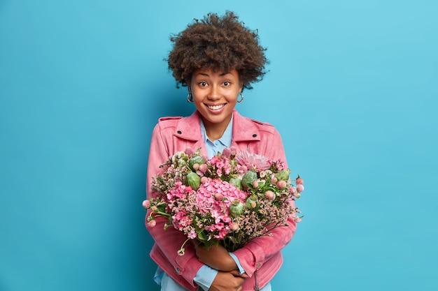 Binnen schot van positieve jonge vrouw omarmt grote bos bloemen glimlacht aangenaam gekleed in roze jas geïsoleerd over blauwe muur