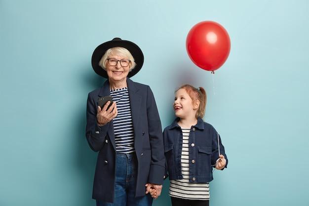 Binnen schot van positieve kleine vrouwelijke jongen houdt luchtballon