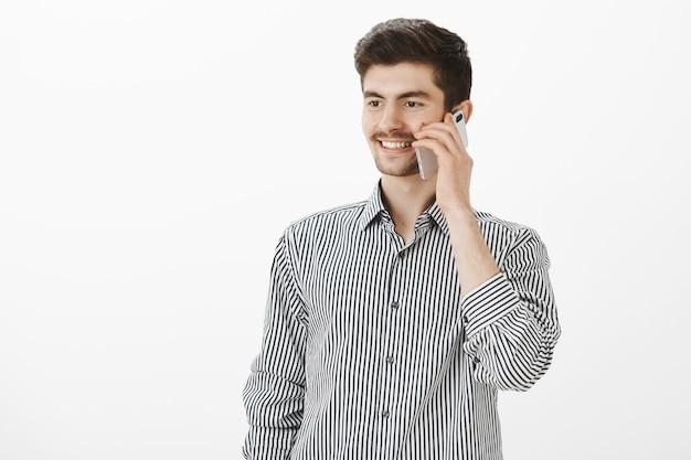 Binnen schot van positieve knappe zelfverzekerde man in gestreept overhemd, praten over smartphone, opzij kijken en glimlachen