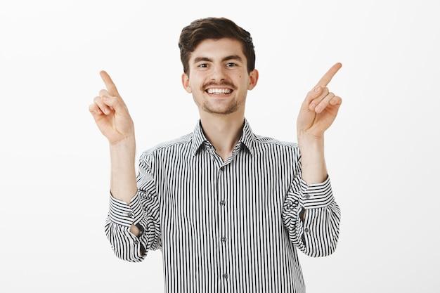 Binnen schot van positieve vriendelijke europese man met mosutache en baard, blij lachend, zorgeloos en gelukkig gevoel, wijsvingers opheffend en wijzend naar verschillende hoeken, staande over grijze muur