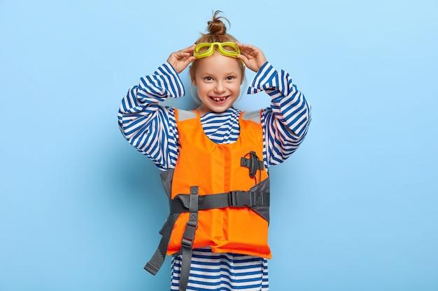 Binnen schot van roodharig meisje poseren in haar zwembad outfit