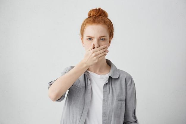 Binnen schot van serieuze jonge blanke vrouw met rood haar, gekleed in vrijetijdskleding die de mond bedekt met de hand als teken van geheimhouding of vertrouwelijke informatie, gefrustreerd voelen
