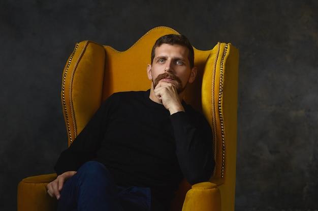 Binnen schot van stijlvolle ongeschoren man in zwarte slijtage ontspannen in gele fauteuil en wrijven zijn baard zittend tegen lege muur met kopie ruimte voor uw inhoud